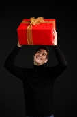 Man in black turtleneck, holding wrapped present over his head - Alex Microstock02