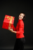 Woman in red turtleneck carrying big red box with gold ribbon - Alex Microstock02