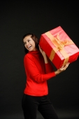 Woman in red turtleneck holding gift, looking away - Alex Microstock02