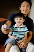 Father with young son on lap, holding TV remote control - Alex Microstock02
