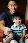 Father with young son on lap, holding TV remote control towards camera - Alex Microstock02