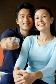 Couple sitting side by side, man holding TV remote control - Alex Microstock02