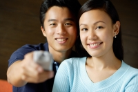 Couple side by side, man holding TV remote control towards camera - Alex Microstock02