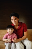 Father and young son sitting on sofa, smiling at camera - Alex Mares-Manton