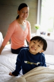 Young boy sitting on bed, smiling at camera, mother in the background - Alex Mares-Manton