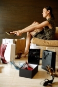 Woman putting on high heel shoes, surrounded by shopping bags, shoes boxes and shoes - Alex Mares-Manton