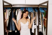 Woman standing in front of wardrobe full of clothes, smiling at camera - Alex Mares-Manton
