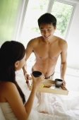 Man bringing woman breakfast in bed - Alex Mares-Manton
