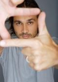 Man looking at camera through his fingers - Yukmin