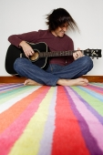 Man sitting on striped carpet, playing with guitar - Yukmin