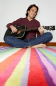Man sitting on striped carpet, holding guitar, smiling at camera - Yukmin