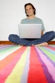 Man sitting on striped carpet with laptop, looking at camera - Yukmin