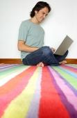 Man sitting on striped carpet, using laptop - Yukmin