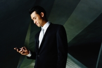 Businessman looking at mobile phone - Yukmin