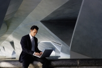 Businessman sitting on ledge, using laptop - Yukmin