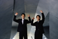 Two businessmen looking at camera, hands raised in the air - Yukmin