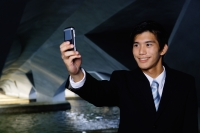 Businessman in tunnel, taking a picture of himself with camera phone - Yukmin