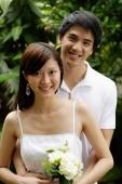 Couple standing in garden, smiling at camera - Alex Mares-Manton
