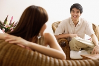 Couple at home in living room, woman turning to look at man - Alex Mares-Manton