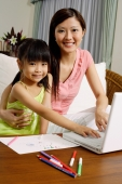 Mother and daughter with laptop, looking at camera - Alex Mares-Manton