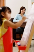 Mother watching young girl painting on easel - Alex Mares-Manton