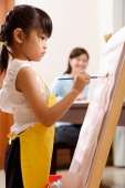 Girl painting on easel, mother in the background - Alex Mares-Manton
