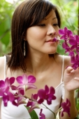Young woman smelling orchids - Alex Mares-Manton