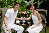 Couple sitting in garden, holding hands, smiling at camera - Alex Mares-Manton