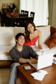 Couple in living room, using laptop, looking at camera - Alex Mares-Manton