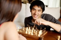 Couple in living room, playing chess, man facing camera - Alex Mares-Manton