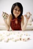 Young woman holding mahjong tiles - Alex Mares-Manton