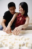 Couple arranging mahjong tiles on the table in front of them - Alex Mares-Manton