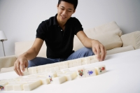 Man arranging mahjong tiles on the table - Alex Mares-Manton
