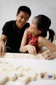 Couple arranging mahjong tiles, smiling - Alex Mares-Manton