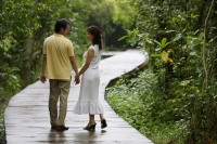 Mature couple walking along path in park, holding hands - Alex Mares-Manton