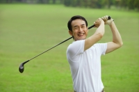 Man swinging golf club, smiling at camera - Alex Mares-Manton