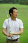 Man holding golf club, looking away - Alex Mares-Manton