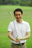 Man holding golf club, looking at camera - Alex Mares-Manton