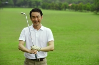 Man holding golf club, smiling at camera - Alex Mares-Manton