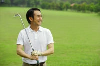 Man holding golf club, smiling, looking away - Alex Mares-Manton