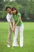 Couple playing golf, looking at camera - Alex Mares-Manton