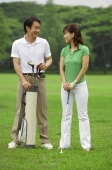 Man standing with golf bag, smiling at woman next to him - Alex Mares-Manton
