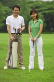 Couple with golf club and golf bag, smiling at camera - Alex Mares-Manton