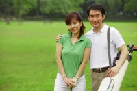 Couple standing side by side on golf course, looking at camera - Alex Mares-Manton