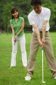 Couple on golf course, woman copying man's stance - Alex Mares-Manton