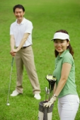 Couple on golf course, smiling at camera - Alex Mares-Manton
