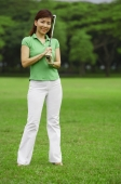 Female golfer with golf club, looking at camera - Alex Mares-Manton