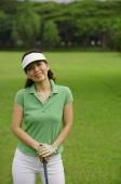 Female golfer with golf club, smiling at camera - Alex Mares-Manton