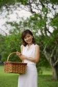 Woman carrying picnic basket, smiling at camera - Alex Mares-Manton
