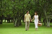 Couple walking in park, woman carrying picnic basket - Alex Mares-Manton